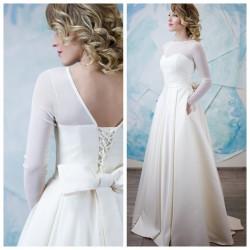 vestuvine suknele su ilgom rankovem, dideliu kaspinu nugaroje